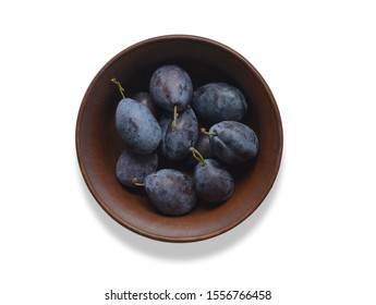Blue plums.  Fresh plums in a ceramic plate close-up on the table. Слива.