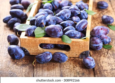 blue plums in a wooden box