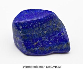 Blue polished shiny lapis lazuli stone mineral specimen with golden inclusions isolated on white limbo background