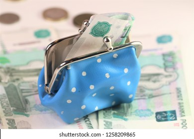 a blue polka dot open woman purse; coins stack; banknotes, money background