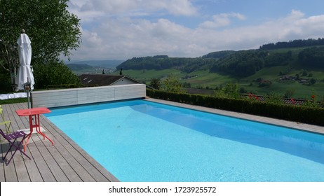 Blue pool with landscape in the background, pool with wood floor above. Pool with chair and table, sunshine and warm temperature in the summer
