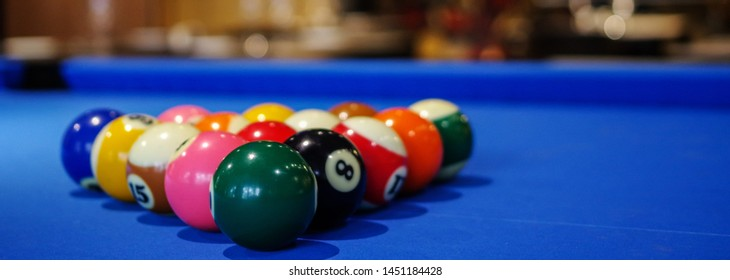 Blue pool table and billiard balls set up. Restaurant tables with wineglasses as background