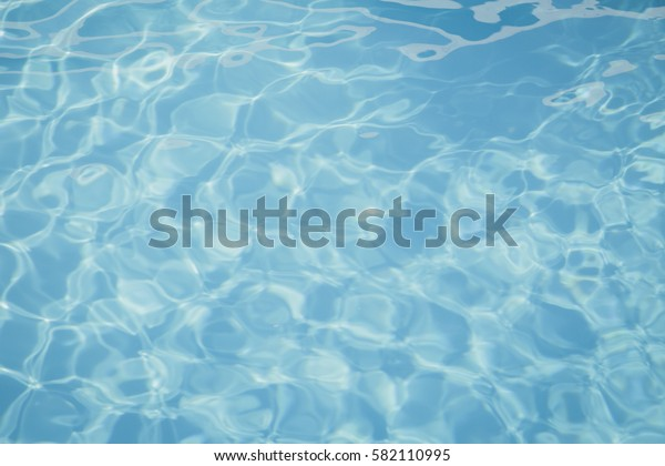Blue pool water with sun reflections background