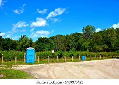 Blue portable outhouse at the end of a parks parking lot matching the color of the clouded sky.  The outhouse is available for use during the summer months.  There is a woods and savannah area behind.
