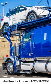 Blue powerful industrial grade big rig car hauler semi truck transporting cars on two levels hydraulic semi trailer running on the road with concrete wall on the side