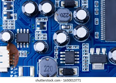 Blue printed Circuit Board with microchips and many electrical components.  capacitors close up