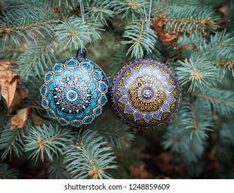 Blue and purple new year balls covered with hand drawn abstract mandalas hanging on Christmas pine tree.  Holiday background.