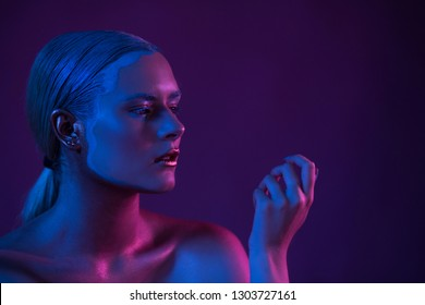 Blue Purple Portrait of Sexy Naked Model in Neon Light on Dark Background. Creative Make Up Concept.
