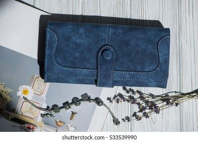 Blue purse near the bracelet, lavender on a white background.