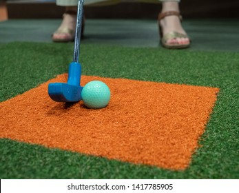 Blue putter on turf lined up next to green golf ball on miniature golf course with a woman playing