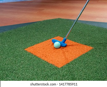 Blue putter on turf lined up next to green golf ball on miniature golf course