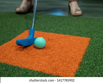 Blue putter on turf next to green golf ball on miniature golf course with a woman hitting