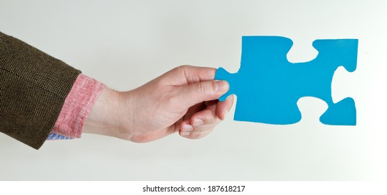 blue puzzle piece in male hand on grey background