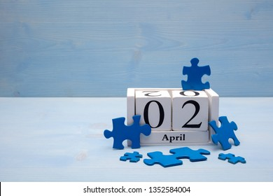 Blue Puzzle Pieces Standing with calendar on wooden background