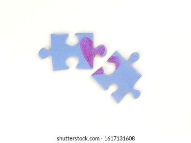 Blue puzzle with a red heart on the white isolation background. Two disconnected puzzle halves. Valentine's day stock photo with empty space for text.For web, print, postcard, background and wallpaper