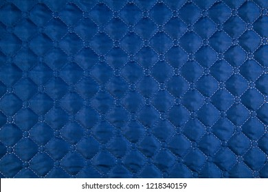 Blue quilted fabric. The texture of the blanket