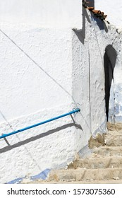 A blue railing attached to a white building above a flight of stairs in the Medina of Chefchaouen, Morocco, which is also known as Chaouen and The Blue City.