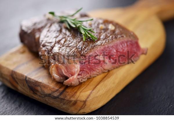 Blue rare steak on cutting board