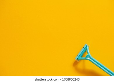 Blue razor on a yellow background top view. The concept of hygiene, beauty, shaving.