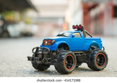 Blue RC Off road truck car (Radio-controlled) on the asphalt ground. This toy have some dust from children playing.