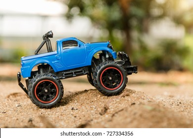 Blue RC Off-road truck car (Radio-controlled) standing on the terrain sand dune. This toy has some dust from children playing.