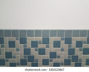 blue rectangle and square tiles on bathroom wall