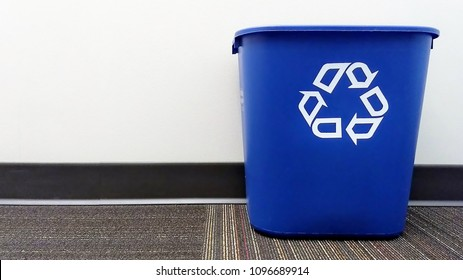 A blue recycle bin sits on the floor of an office.