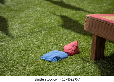 Blue and red bean bags beside a wooden corn hole set, on an artificial grass lawn with space for text on the left