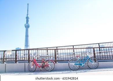 墨田川沿いの道の橋の手すりにある青と赤の自転車公園は、東京・浅草の対岸にある東京スカイツリーを見る。