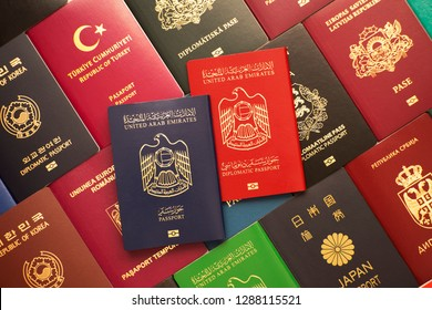 Blue and red biometric passports of United Arab Emirates on background of various documents of many countries of the world