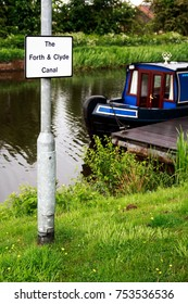 Blue and red canal boat moored in the Forth & Clyde Canal, Scotland