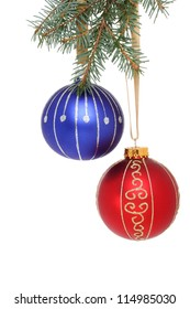 Blue and red Christmas baubles hanging from a branch of a Christmas tree
