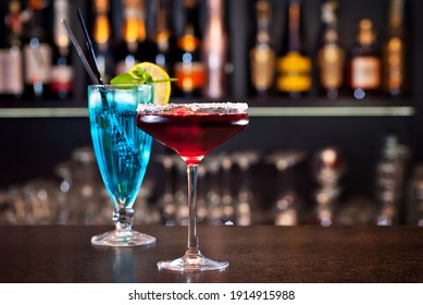 Blue and red cocktails on the bar. Alcoholic cocktails on a background of shelves with bottles. Blurred bottles of alcohol on the wall of the bar.