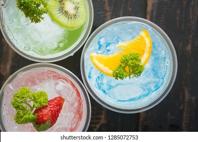 Blue Red Green Italian Soda Cold Beverage and Lemon Strawberry Kiwi Fruit and Parsley. Blue Red Green Italian Soda Cold Beverage on wood table for food and drink category