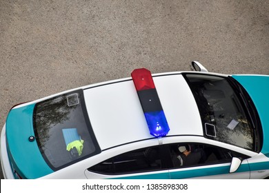 Blue and red light flasher atop of a police car, top view from the window (view from above) of a house or building. Evening time, Kazakhstan