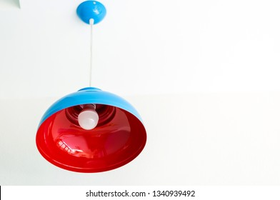 Blue and Red Metal Lamp Hanging on a Wall