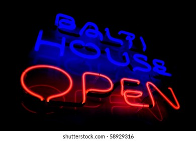 Blue and red neon sign of the words 'Balti house open' on a black background.