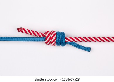 Blue and red nylon rope in double fishermans knot on white