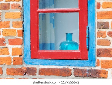 Blue and Red Painted Window in Brick Wall with Blue Glassware