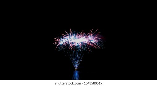 Blue, red, and pink fireworks partially reflected on the water