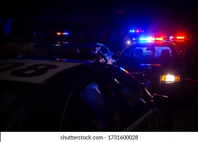Blue and red police lights on squad cars during a night time traffic stop, with space for text on the left