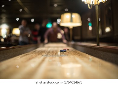 Blue and red puck on a shuffleboard table