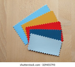Blue red yellow paper swatch with zig zag border cut with pinking shears