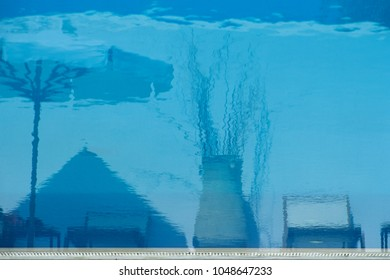 Blue reflexion of chairs, sunshade and a vase at pool water