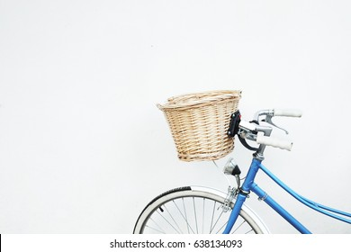 Blue retro bicycle with basket on white wall.