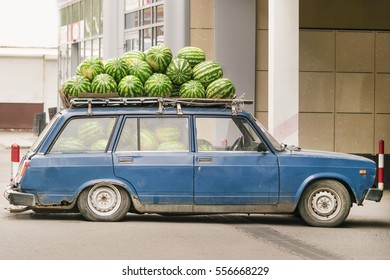 Blue retro car with watermelons on the roof on a city street