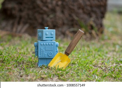 Blue Retro robot toys with garden tools in Natural green leaves background.