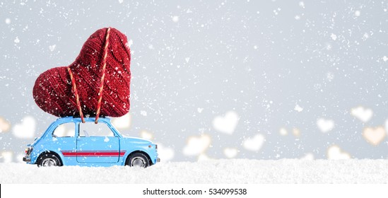 Blue retro toy car delivering heart for Valentine's day on gray background