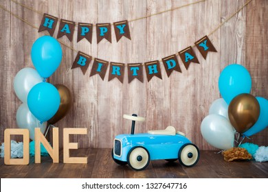 Blue retro toy car with helium balloons on a wooden background. Children's holiday decorated photo zone for a little boy. Happy birthday, 1 year.