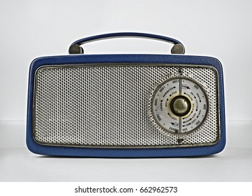 Blue retro vintage transistor radio shot straight on in a studio setting with a white background.